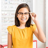 Cute little school girl wearing oversized spectacles and laughing at optical store while looking at camera